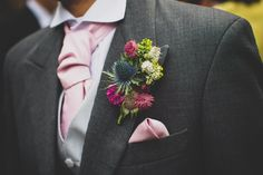 A thistle wild flower buttoneer button hole with pinks, lilacs and fuscia. Groom wears a pink cravat, waistcoat and grey suit with pocket square - photo by tobiah tayo photography - available for commissions worldwide - www.tobiatayo.com