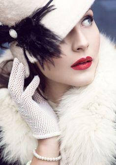 White cloche, airy black feather trim, red lip. Class.  Ana Rosa