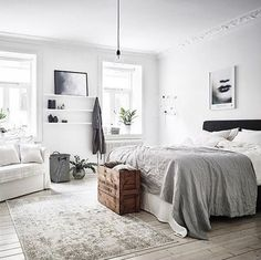 Black and white high contrast color bedroom. Mix of chic and classic design with antique additions like the wooden crate. Black white grey color scheme maintained with black wooden headboard, white pillows and a soft grey duvet. White shelf adds storage space for photographs, art, small plants, and decorations. Lots of natural lighting