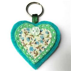 Sweet little heart keyring . This little heart keyring also looks great as a bag charm :) It features a floral fabric heart in the centre, mounted onto a light green felt heart with a turquoise felt base using a visible running stitch in a cream thre. Fabric Crafts, Sewing Crafts, Felt Keychain, Keychains, Diy Keyring, Turquoise Christmas, Little Presents, Felt Decorations, Heart Crafts