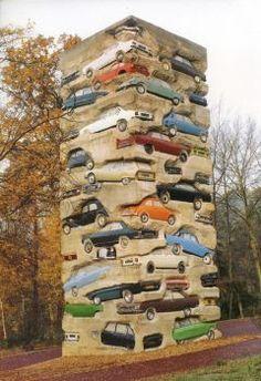 ARMAN, Long term parking       1976, tour composée d'empilement de voitures coulées dans du béton. 19.50m de haut, 59 voitures. Selon les vœux d'Arman, l'œuvre devrait partir en miette au fil des ans, les pneus puis les carcasses s'effritant, ne laissant plus que leur empreinte dans le béton, pour que celui-ci disparaisse enfin.