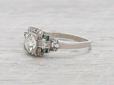 Art Deco vintage engagement ring made in platinum and centered with a .99 carat GIA certified old European cut diamond with I color and SI1 clarity. Accented by single cut diamonds and calibre cut emeralds. Circa 1920