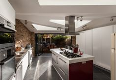 Triangular roof lights on the Cassland Road property send light deep into the plan, while casting constantly changing light patterns over the floor, walls and kitchen units.