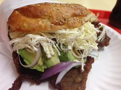 Cemita -a torta originally from Puebla, Mexico. The word refers to the sandwich as well as to the roll it is typically served on, a bread roll covered with sesame seeds. The bread is made with egg, and resembles brioche. Additionally, the ingredients usually are restricted to sliced avocado, meat, white cheese, onions, the herb pápalo and red sauce (salsa roja). In modern times it has appeared on the streets of New York, Los Angeles, and other cities with Mexican food vendors.