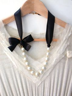 Inspired by my favorite - Carrie Bradshaw in Sex and The City! Beautiful black satin ribbons are connected to gold plated ovals, white pearls and