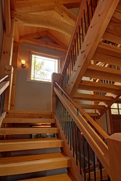 Timber frame home open staircase features a natural beam, cut from a tree on site