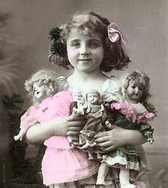 PRETTY GIRL WITH BOW AND FLOWERS IN HER HAIR, AND HER DOLLS.