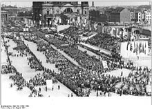 My mother attended the 3rd World Festival of Youth and Students in 1951 Berlin.  She might be somewhere in this picture.  Nikita Khruschev shook her hand here; he was shaking the hands of all the youth in the first row.  My mother really disliked him and communism, but to throw a revolt here would be death.  She later escaped after protesting and be placed a on list for pick up and possible transportation to a Siberian prison camp.