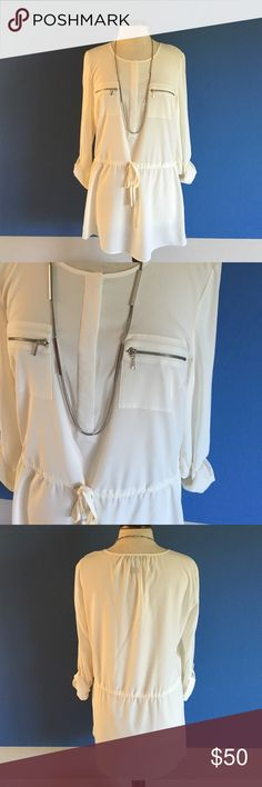 "🆕 INC Cream Blouse NWOT - This blouse is sure to stand out in the crowd.   There are hidden buttons at the top middle.  Silver zippers are placed on the breast pockets.  There is also a tie at the waist for the perfect fit.  Sleeves can be worn 3/4 or down.  Pair with leggings and boots and you have a great outfit.  Material: 97% Polyester/3% Spandex. Measurements:  Length - 31""/Bust - 21""/Waist - 20"" Max (can be tightened with tie) INC International Concepts Tops Blouses"