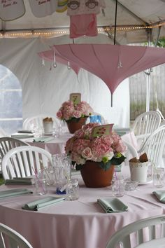 """Its a """"baby shower!"""" buy inexpensive umbrellas, hang upside down with clear string across tent-then hang crytal raindrops for """"shower"""" theme around the umbrella to hang above each table-finish off with potted planters with hydrangas for a summer garden themed party"""