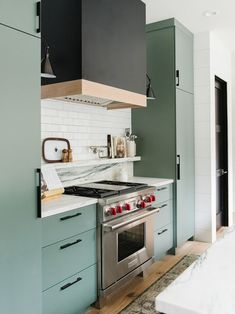 black and brass range and sage green kitchen cabinets
