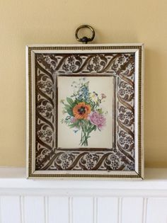 This is a beautiful cream & gold wood frame with a 3D ( blow mold ) floral picture & original glass. Done in colors of orange, pink, blue & green. Lots of details on frame & picture with a gold metal round decorative top finial. Back reads RELIANCE INDUSTRIES CHICAGO, ILLINOIS Style # 606 glass size 6 x 7. In good vintage condition with some wear to paint on frame. Only adds to the vintage charm! Makes a great statement wall decor item paired with other floral pictures or mirrors. Measures…
