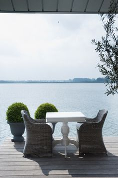 urns of box ball topiary, wicker chairs outside perfection and what a view!