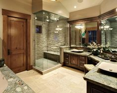 Stone and wood bathroon. Stone bench in shower. Make-up bench. His/Her sinks.