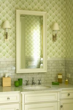 Beautiful ivory & green bathroom design with green wallpaper, ivory beveled mirror, white carrara marble subway tiles backsplash and counter top, ivory bathroom cabinet vanity and kelly green bathroom accents.