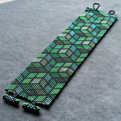 This peyote pattern is for a Green Mosaic bracelet using size 11 Delica beads. This pattern will include: *Bead Legend *Full Color Bead Chart *Word Chart Pattern Details: Width: 1.54 (29 columns) Length: 6.92 (200 rows) (pattern length only, does not include clasp length) Number of Colors: 13 Bead Type: Size 11 Miyuki Delicas Stitch Used: Peyote (odd count) This pattern can easily be shortened by omitting rows on one or both ends. I always test my patterns to ensure color acc...