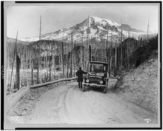 A Detroit Electric automobile stopped on road by burnt-over land, with snow-covered mountain in background, Washington