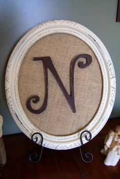 Initial in oval frame on burlap