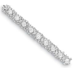 A DIAMOND BRACELET, BY HARRY WINSTON.    Designed as a pear-shaped diamond cluster band set with nine square-cut diamonds, weighing from approximately 4.44 to 5.73 carats, mounted in platinum, circa 1971, 7½ ins., in a Harry Winston black suede case. By Harry Winston, no. 7601.