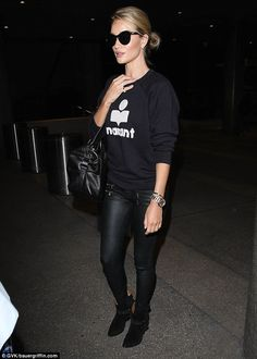 Jet-set: The 28-year-old stunner nailed low-key glamour as she wore head-to-toe black, in wet-look jeans, a sweatshirt and oversized sunglasses