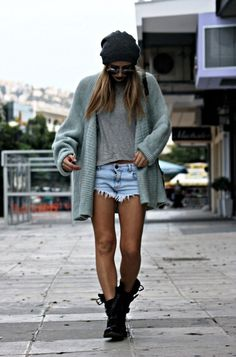 combat boots, cutoffs, beanie, and oversized cardigan