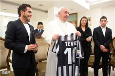 Pope Francis receives a signed football shirt from Carlos Tevez who plays for Juventus and previously with Manchester City and Manchester United.