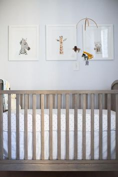 Lovely boy's nursery features a safari animal mobile by Etsy Patricija and baby animal art by The Animal Print Shop placed above a gray stained crib, Land of Nod Archway Crib, dressed in Serena & Lily Pin Dot Crib Sheets.