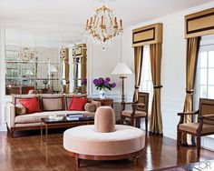 In the formal living room, the cocktail table, sofa, pouf, and armchairs are by Todd Hase  Furniture, the couple's firm, as are the upholstery and the curtain fabric.     - ELLEDecor.com