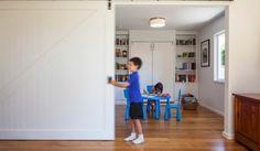 salle de jeux aménagée avec une bibliothèque murale, table et chaises bleues et…