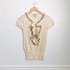 Banana Republic top Knit ivory top with front ruffle with contrasting trim in black. Short sleeves. 100% cotton. Excellent used condition. Size S. Banana Republic Tops