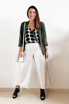 Carol Burgo veste look de outono composto por uma calça pantacourt prateada da Zara, bolsa branca da C&A, parka verde militar de linho da C&A, blusa de bolas preta e branca em seda, da Animale, sandália preta de couro tratorada da Arezzo.