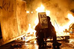 Here Are The Most Powerful Photos From The Ferguson Protests-- A demonstrator sits in front of a debris fire in Ferguson.