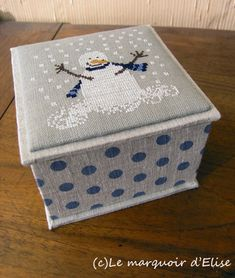"""Une petite boîte en cartonnage maison ornée d'un bonhomme de neige (grille d'H. Wind, in Country au point de croix"""", Marabout, 2007)"""