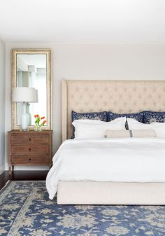 Bedroom. Master Bedroom. Blue and white decor in master bedroom. This stunning cream and blue bedroom features a linen tufted wingback bed dressed in white bedding and blue pillows next to a French nightstand. The headboard is from Restoration Hardware. The rug is from ABC Carpet in NYC. The master bedroom bedding is from Pottery Barn. Nightstand is from Arteriors Home. Mirror above night stand is from Ballard Designs #MasterBedroom #Bedroom #Decor Chango & Co.