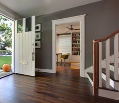 Love everything about this entry way...the front door, the grey walls, the borders, floors and stairs!