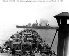 """Sicily Invasion, July 1943 USS Boise (CL-47) fires on enemy forces near Gela, Sicily, on 11 July 1943. Photographed by Sgt. Crosnon from USS LST-325. Note manned .50 caliber machine guns on several of the Army trucks embarked on the LST's deck, a precaution against German air attack. Morison, """"History of U.S. Naval Operations in World War II"""" (Vol. IX, page 107) states that Boise's targets were enemy tanks."""