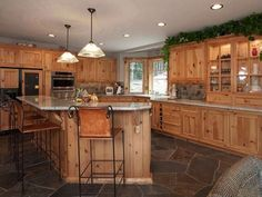 Rustic Kitchen - the knotty alder cabinets and natural stone floor makes this a beautiful, warm kitchen. Love the wood on the bar. Knotty Alder Kitchen, Knotty Alder Cabinets, Hickory Kitchen Cabinets, Refacing Kitchen Cabinets, Rustic Cabinets, Inset Cabinets, Cupboards, Rustic Shelves, Dark Cabinets