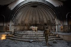 A fighter from the NPU (Nineveh Plain Protection Units) walks through a destroyed church on November 8, 2016 in Qaraqosh, Iraq. The NPU is a military organization made up of Assyrian Christians and was formed in late 2014 to defend against ISIS. Photo by Chris McGrath / Getty