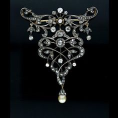 Antique silver over 14K gold small stomacher with flowing floral and foliate design that foreshadows the whiplash lines of Art Nouveau. This piece is set with eleven old mine cut diamonds (1.00 carat total weight, H-K color, SI clarity) and 153 rose cut diamonds (2.00 carats total weight) with a dark grey cream pearl drop (6.75 X 7.5 mm), circa 1900.