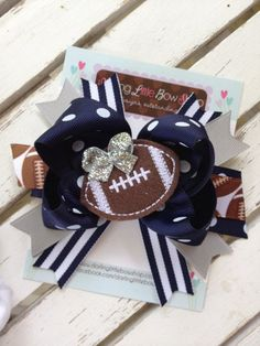 Football bow with optional headband. Shown in navy and silver, but can be made in your team colors. Choose team colors or leave a note at