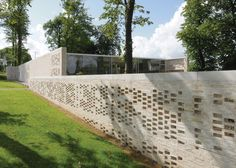 A perforated brick wall encloses a series of internal courtyards and gardens at the latest Maggie's Centre for cancer care.