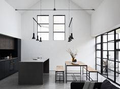 Large steel framed windows and doors frame the open kitchen and dining space.  Modern pendant lights hang above each cooking and eating surface.  Tagged: Kitchen, Pendant Lighting, Concrete Floor, Wall Oven, Marble Backsplashe, Marble Counter, and Wood Cabinet.  Photo 6 of 12 in A Forgotten Warehouse Is Reborn Into a Light-Filled London Home