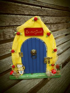 Beauty and the Beast-themed, hand-painted, wooden, hinged fairy door. Framed in yellow organza and red roses - with teacup and preserved rose decorations as well as Be Our Guest door plaque. All our fairy doors are hand-painted, given a shabby chic worn effect on the edges before