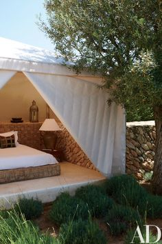 Framed by Ibicencan stone, a tented outdoor guest room is furnished with a woven-raffia platform bed.