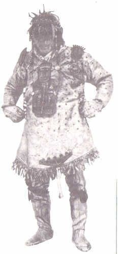 """Regalia of a Yukaghir shaman. The large metal ongons on the shoulders, chest, and groin are a reminder of the other name for the shaman costume, boo huyag, """"shaman armor."""" The ongon at the groin showing several spirits in a canoe, is found in the drum paintings of Sami shamans and the mangee ongons of the Evenks and eastern Mongols, as well as the often deformed images of masters of disease in the Buryat zuragtan ongons. The Yukaghir live exactly at the center point between these peoples."""