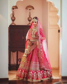 Looking for Bride in red and gold bridal lehenga with floral motifs? Browse of latest bridal photos, lehenga & jewelry designs, decor ideas, etc. Indian Bridal Outfits, Indian Bridal Lehenga, Indian Bridal Fashion, Indian Designer Outfits, Indian Dresses, Wedding Outfits, Wedding Dresses, Designer Dresses, Wedding Lehnga