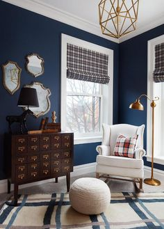 SuzAnn Kletzien - Country cabin boy's nursery features blue walls lined with a white wingback brass nailhead rocker, PB Kids Thatcher Rocker Bronze Nailheads, placed in front of windows dressed in gray plaid roman shades illuminated by a a brass floor lamp from Urban Outfitters next to a vintage style library chest, The Land of Nod Circulation Chest.