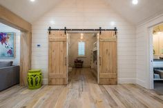 Two barn doors on rails open to boy's room filled with a built in bunk beds equipped with a white ladder alongside a rustic wood floor.