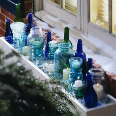 For a striking display cluster colored and clear glass bottles, jars, and vintage insulation glass in an outdoor window box. Vary heights, shapes, and colors for visual interest. Insert votives or flickering battery-operated candles Christmas Window Boxes, Winter Window Boxes, Christmas Window Decorations, Bottle Decorations, Outdoor Decorations, Indoor Window Boxes, Window Sill, Room Window, Bottles And Jars