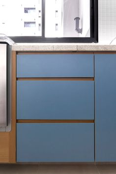 Detalhe de marcenaria para cozinha combinado com madeira e fórmica na cor azul petróleo